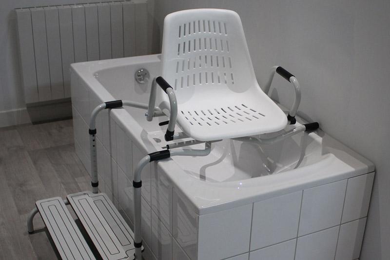 Siège de douche avec accoudoirs et marchepied intégré